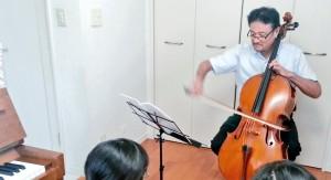 チェロを弾く菊池先生と聴衆